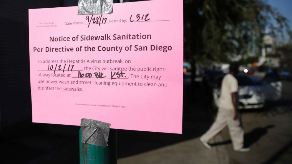A man passes behind a sign warning of an upcoming street cleaning to address a hepatitis A outbreak in San Diego, Sept. 28, 2017.