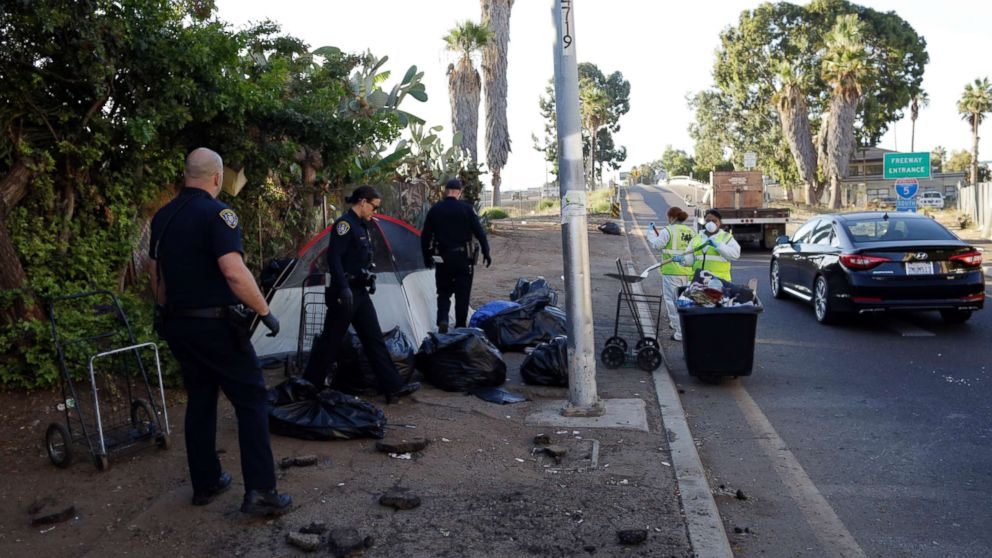 Police officers remove a tent left by the homeless during efforts to sanitize neighborhoods to control the spread of hepatitis A, in San Diego, Sept. 25, 2017.