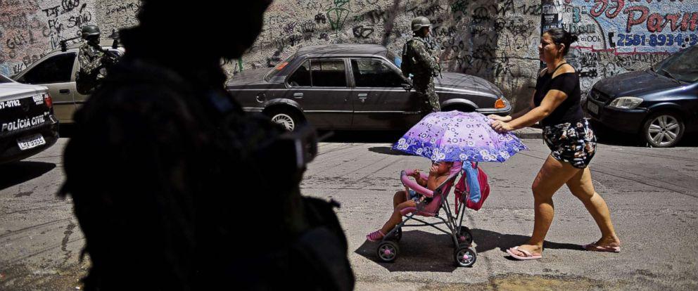 PHOTO: A woman walks past Brazilian military on patrol in Jacarezinho favela in Rio de Janeiro on Jan. 18, 2018.