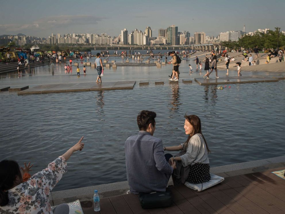 PHOTO: A young couple sits next to a water feature before the Han river and the city skyline, at Yeouido park in Seoul, May 5, 2017.