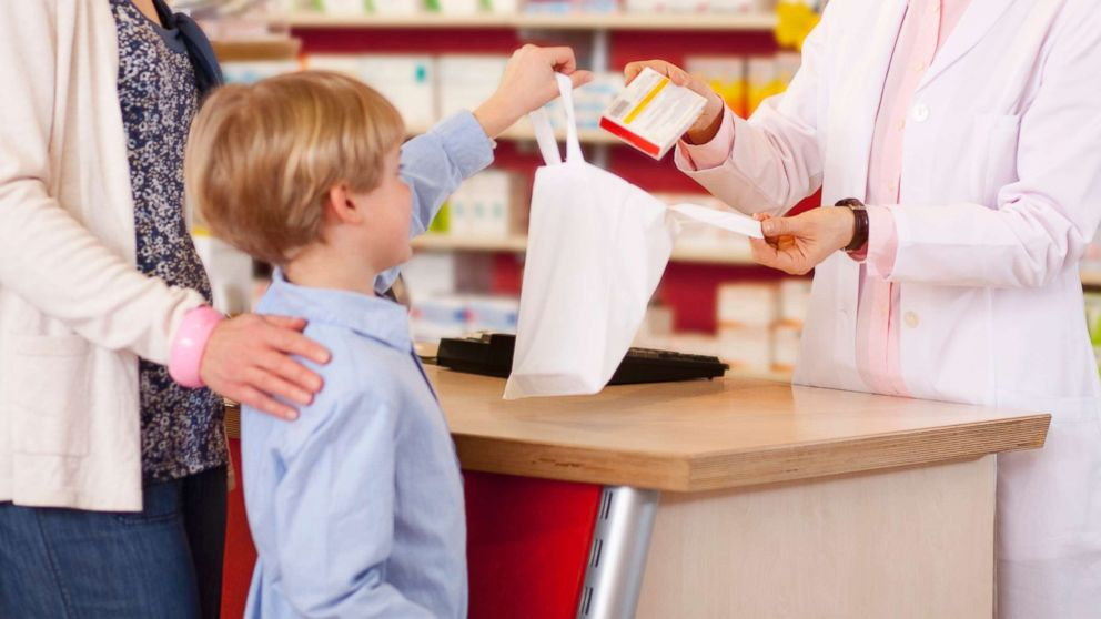 A mother picks up a prescription for her son in an undated stock photo.