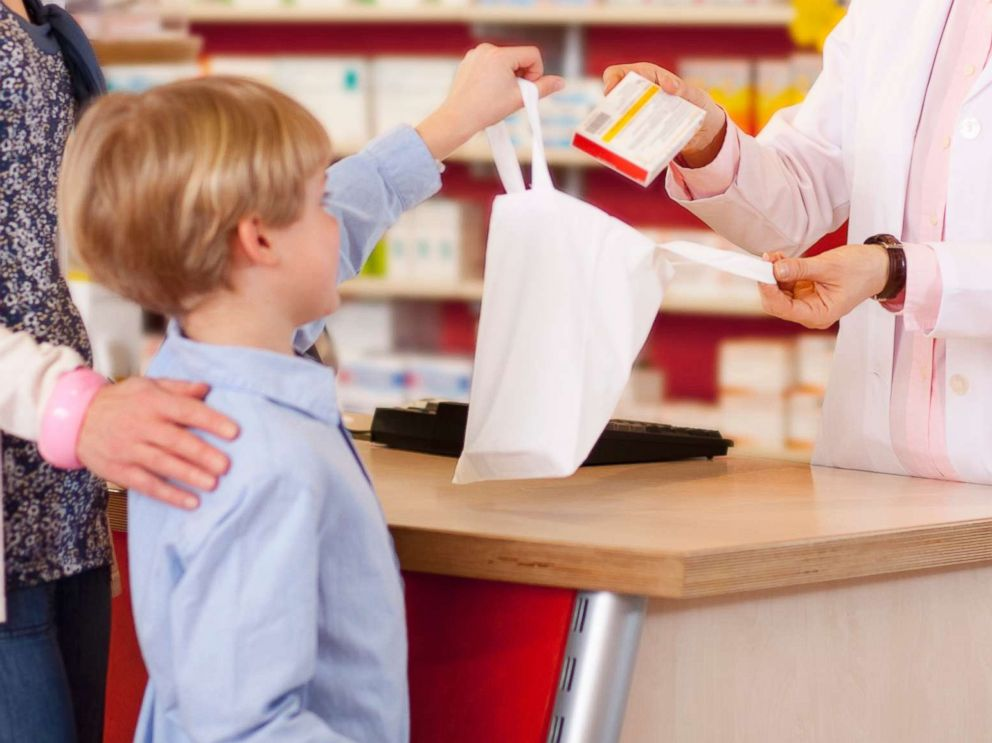 PHOTO: A mother picks up a prescription for her son in an undated stock photo.