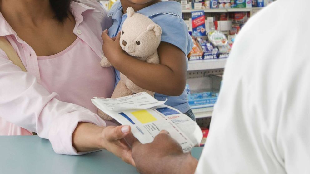 A mother picks up a prescription for her daughter in an undated stock photo.