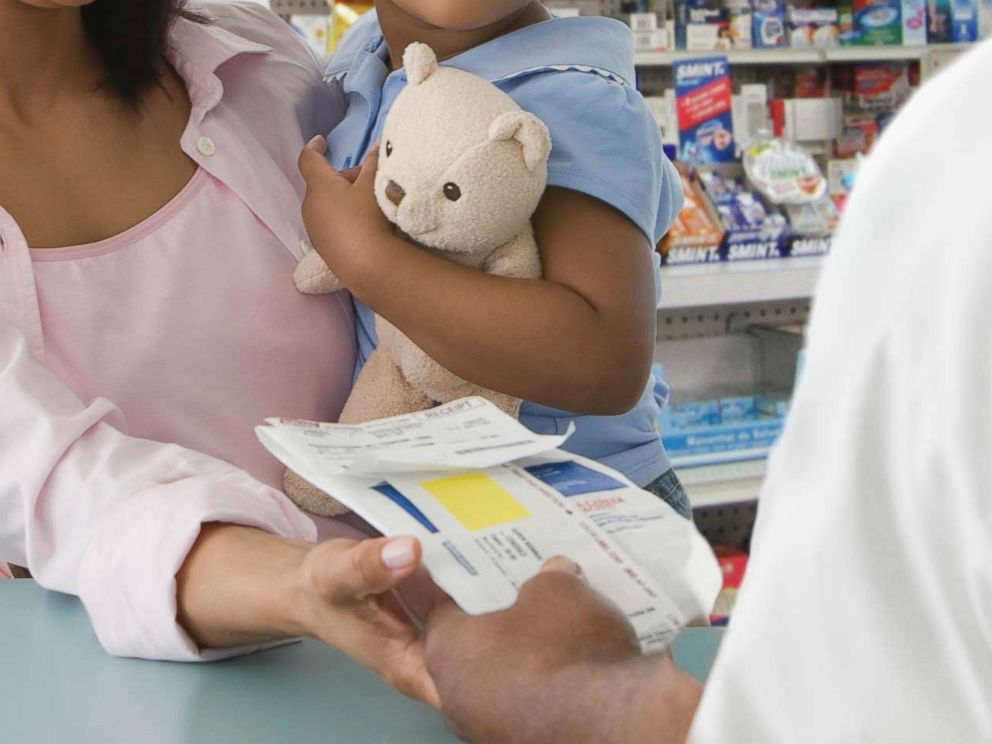 PHOTO: A mother picks up a prescription for her daughter in an undated stock photo.