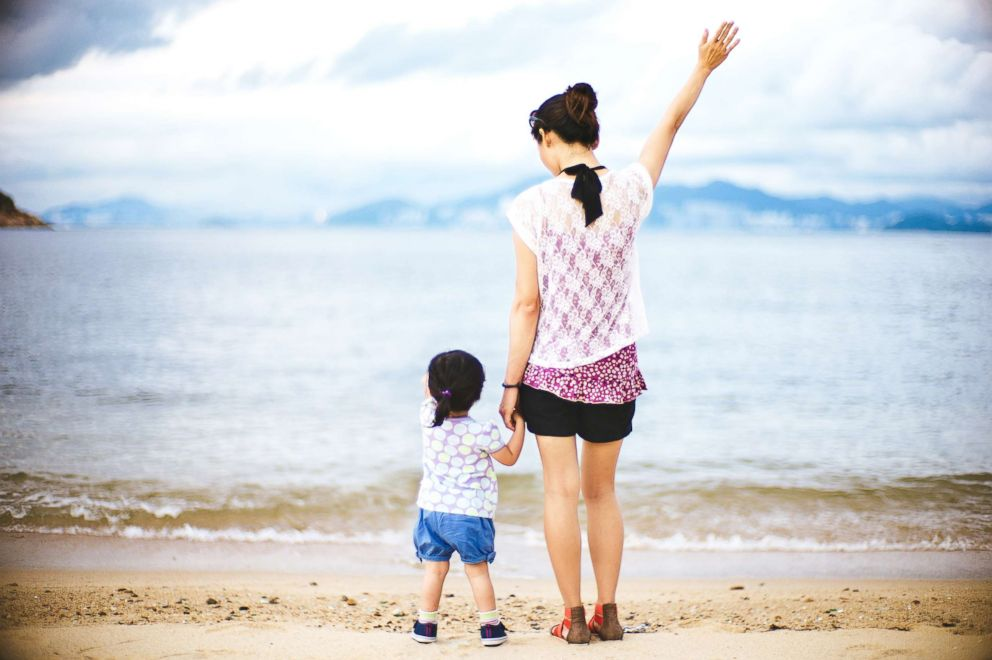 A Young mom and a toddler stand on a beach in this undated stock photo.