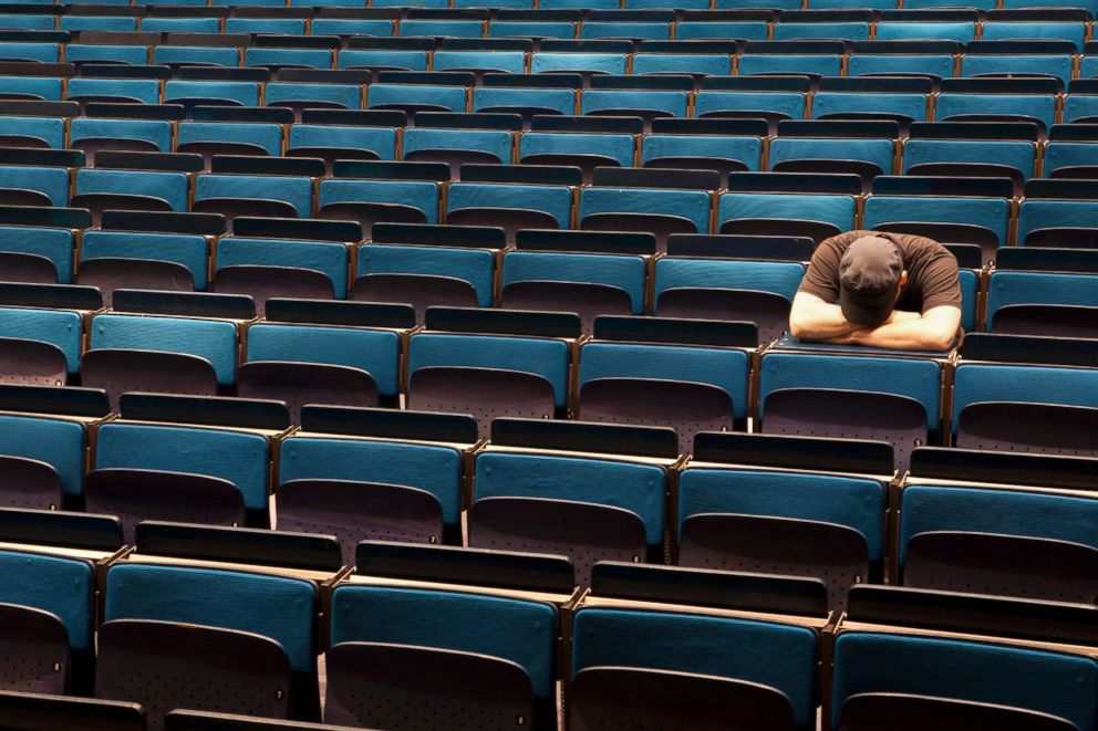 A stressed out student in an auditorium.
