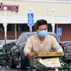 A man wears a facemask while pushing his shopping cart in Alhambra, Calif., Feb. 27, 2020.
