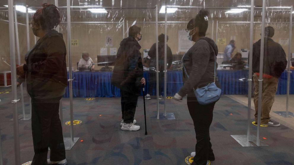 PHOTO: Ohio residents wait in line behind plastic barriers and stand six feet apart to help protect people from Coronavirus during early voting in Toledo, Oct. 6, 2020.