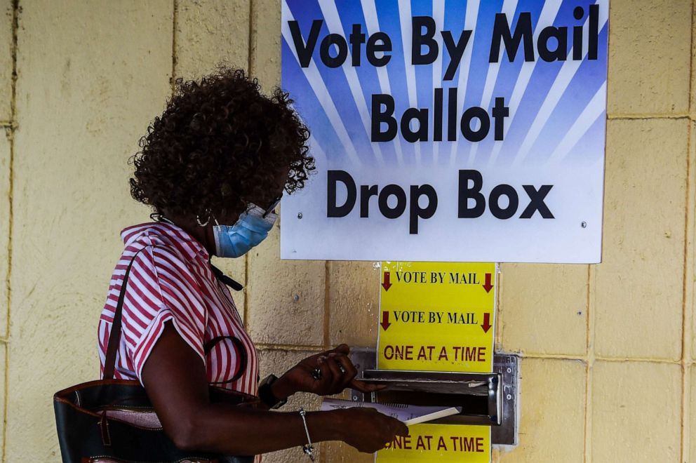PHOTO: A woman drops her ballot by mail at Broward County Supervisor Of Elections Office in Lauderhill, Fla., Oct. 5, 2020.