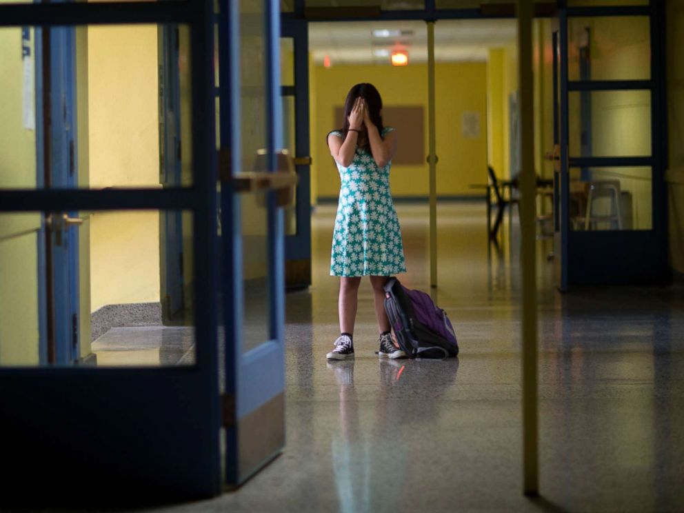 PHOTO: An undated stock photo of a girl in an empty school hallway.