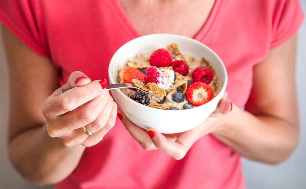 A woman holding a bowl containing homemade granola with oat flakes, corn flakes, dried fruits with fresh berries.