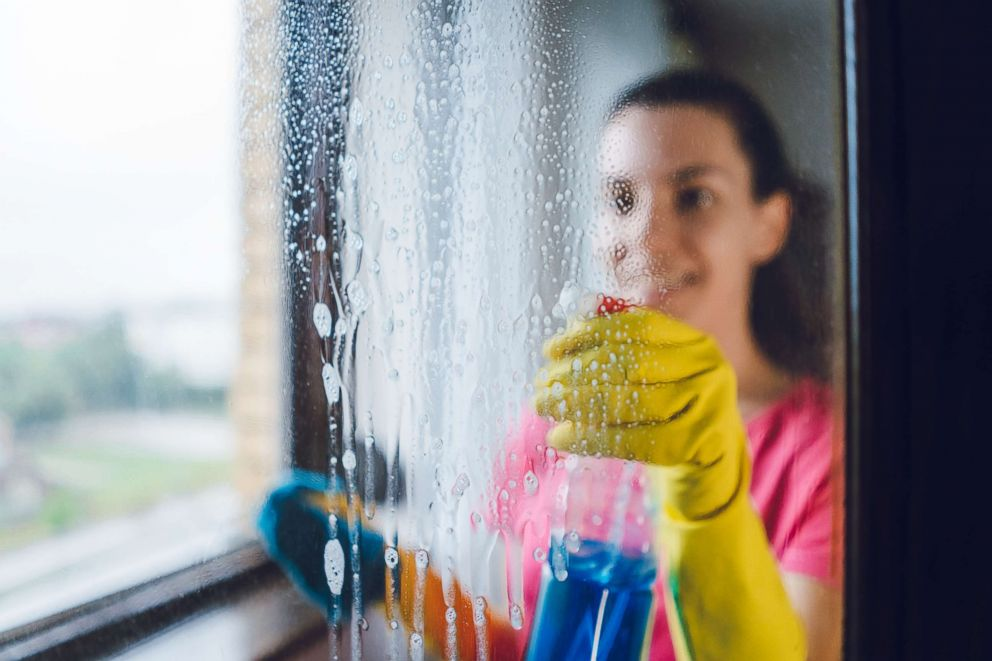 A woman cleans a window in an undated stock photo.