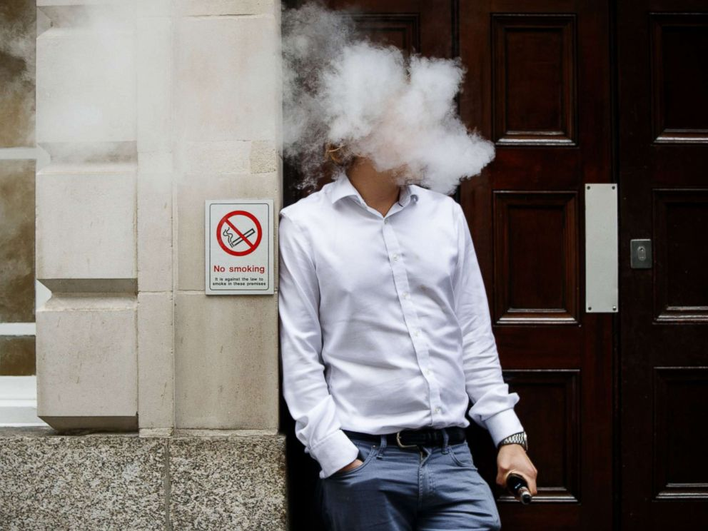 PHOTO: A smoker is engulfed by vapors as he smokes an e-cigarette during lunch time in central London, Aug. 9, 2017.