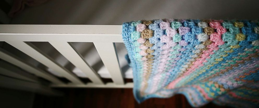 PHOTO: A babys cot and crocheted blanket sit empty in an undated stock photo.
