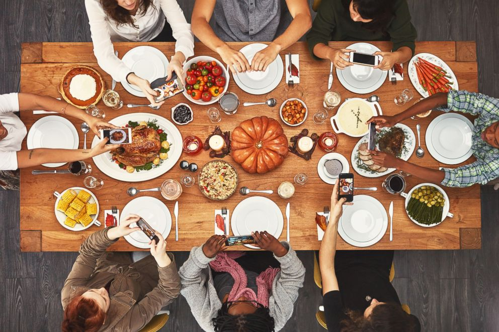 A stock photo depicts people using their phones during a holiday meal.