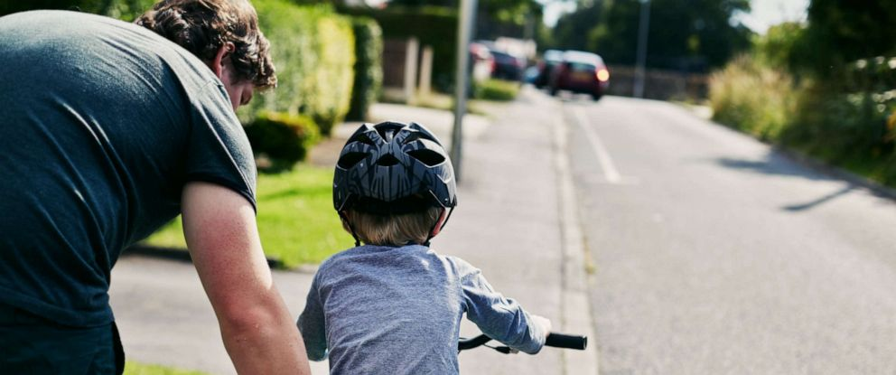 PHOTO: This stock photo depicts a father helping his son learn to ride a bike.