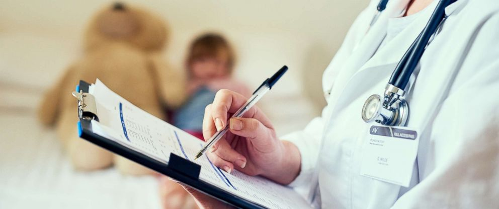 PHOTO: A doctor is pictured filling out a form while treating a child patient in this undated stock photo.
