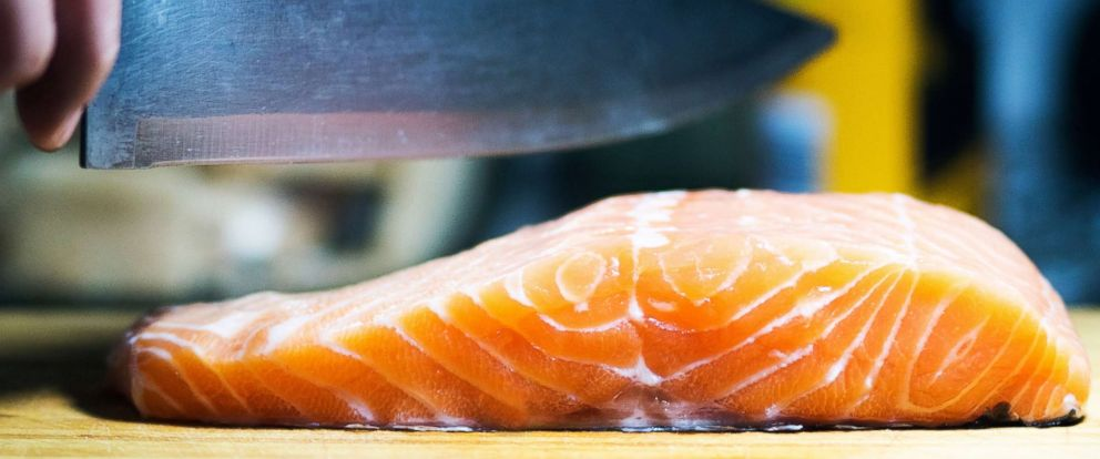PHOTO: This stock photo depicts a chef preparing salmon.