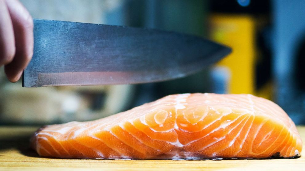 This stock photo depicts a chef preparing salmon.