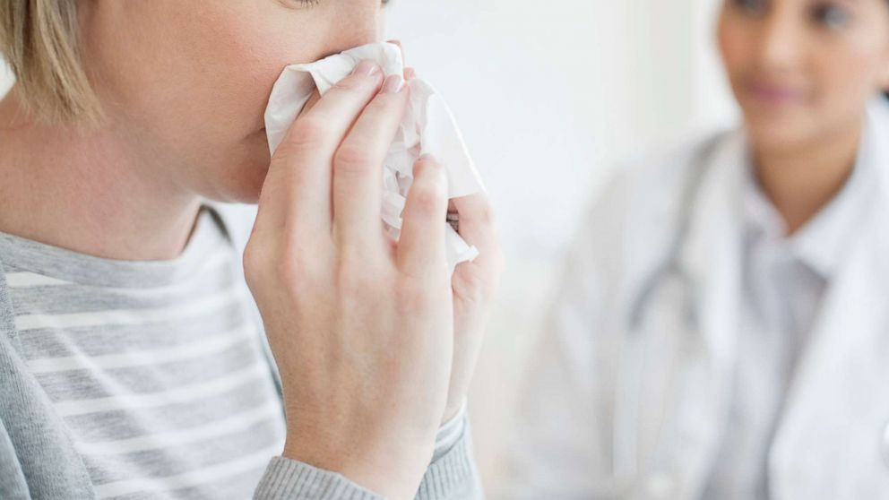 A woman blows her nose in this undated stock image.
