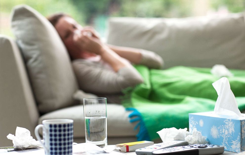 PHOTO: A sick woman lays on a couch blowing her nose in this undated stock photo.