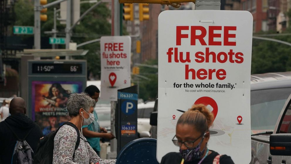 PHOTO: People walk past free flu shot advertisements outside of drugstores on Aug. 19, 2020, in New York.
