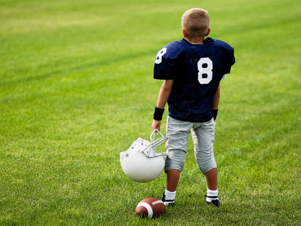 PHOTO: A boy stands in a football field.