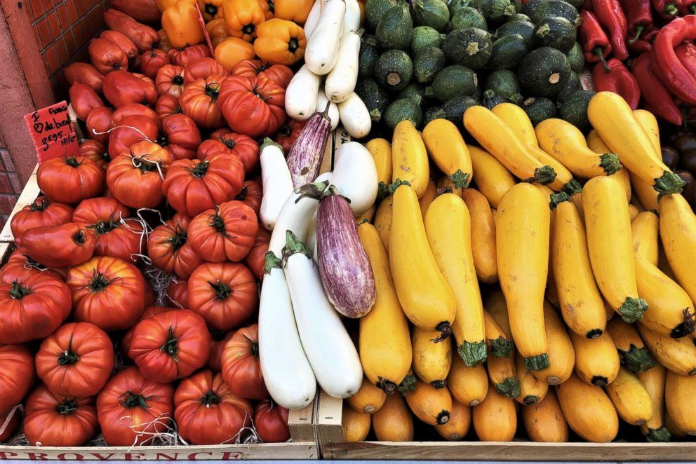 A variety of fruit and vegetables on display in an indoor market.