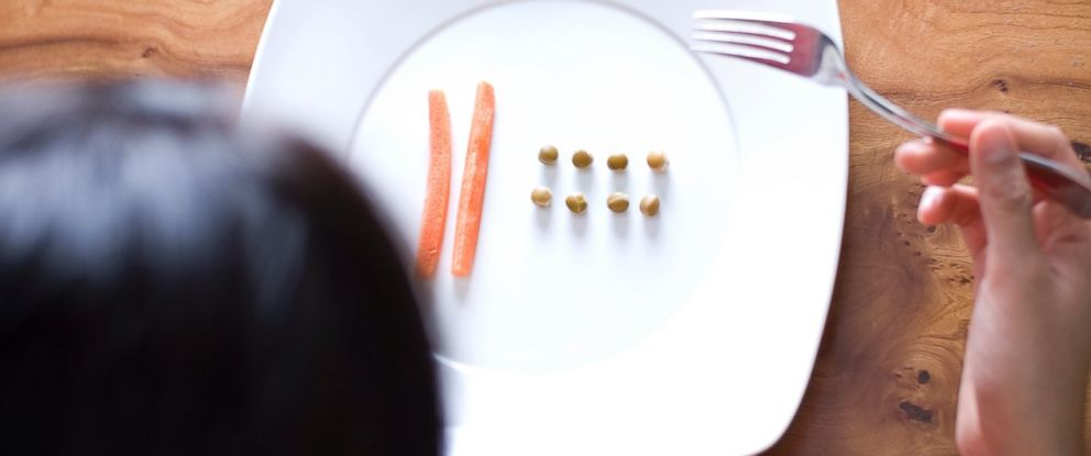 PHOTO: A women looks at food on a plate.