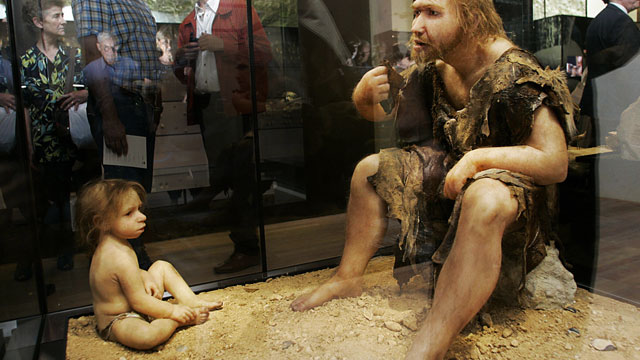 PHOTO: Visitors of the Museum for Prehistory in Eyzies-de-Tayac, France look at a Neanderthal man and child reconstruction.