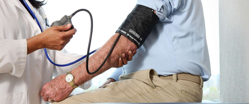 PHOTO: A stock photo depicts a doctor taking a mans blood pressure.