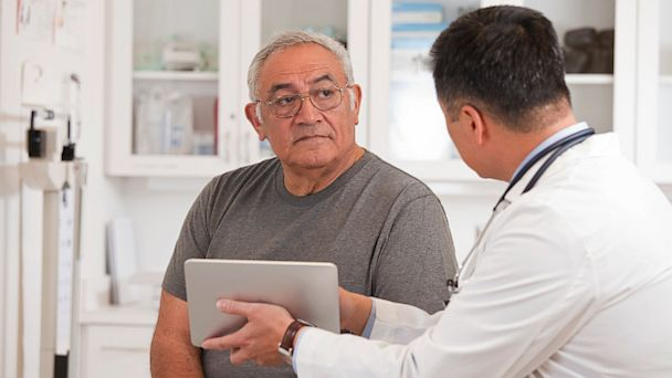 PHOTO: A doctor uses a digital tablet to talk to senior man.