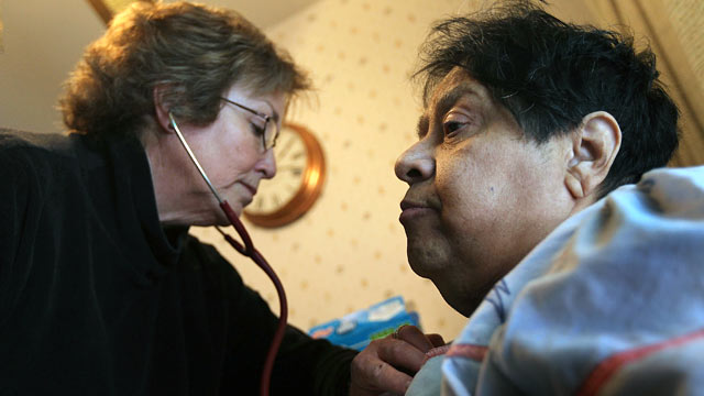PHOTO: Registered nurse Susan Eager, left, checks the breathing of Jane Awise, who suffers from severe diabetes, while performing a home health care visit.
