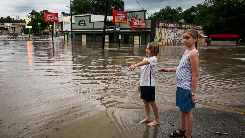 Murphy Canning and Annika Rolston watch as a street remains underwater from days of heavy rain on May 25, 2015 in Austin, Texas.