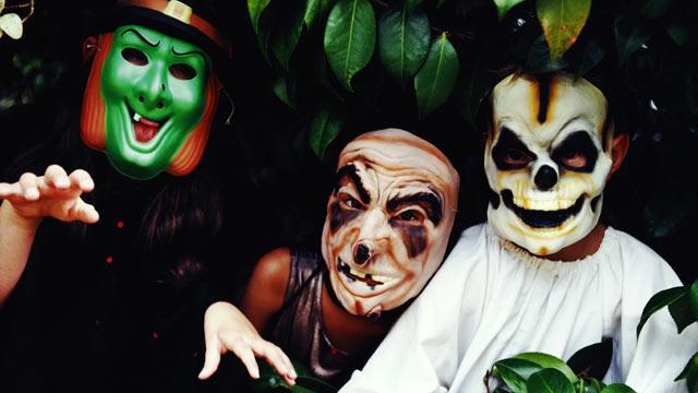 PHOTO: Three children wear halloween masks.