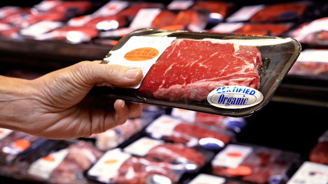 PHOTO: Woman holding packet of beef in supermarket.