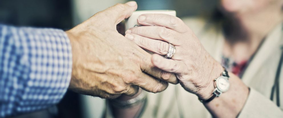 PHOTO: A man hands a mug to a smiling woman in an undated stock photo.