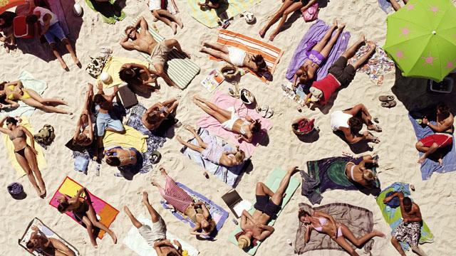 PHOTO: Crowd of people sunbathing on beach.