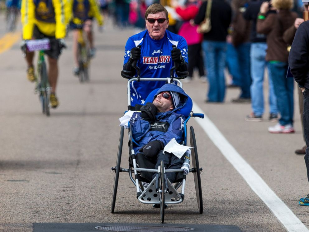 PHOTO: Dick Hoyt pushes his son, Rick Hoyt, in a specialized wheelchair during the 117th Boston Marathon on April 15, 2013.