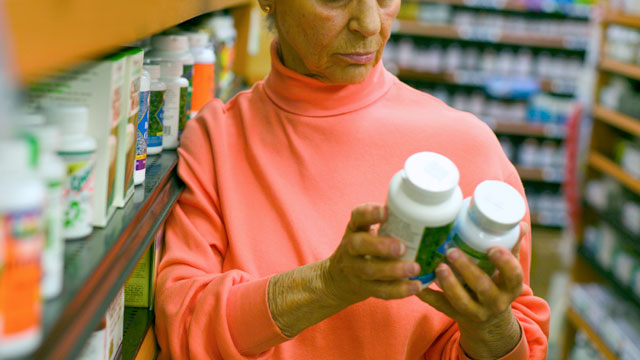 PHOTO: A woman compares vitamins in a pharmacy.