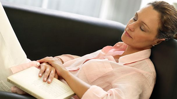 A woman rests on a sofa with a book in hand.