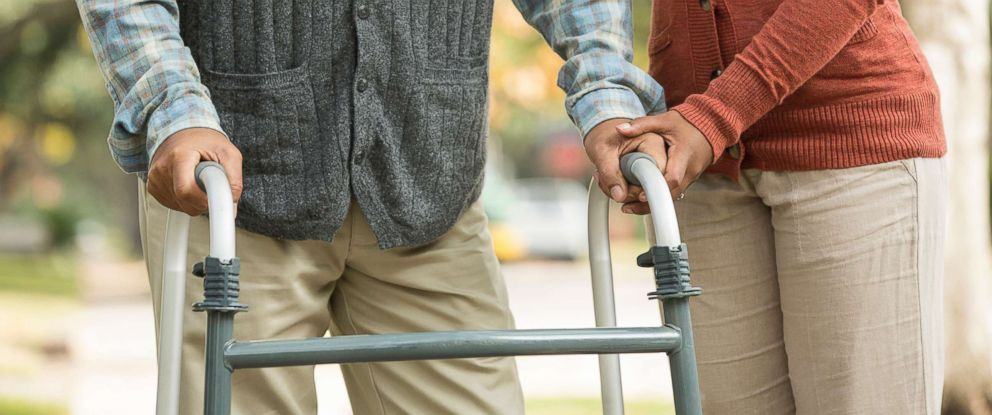 PHOTO: Stock photo of a woman helping her father using a walker.