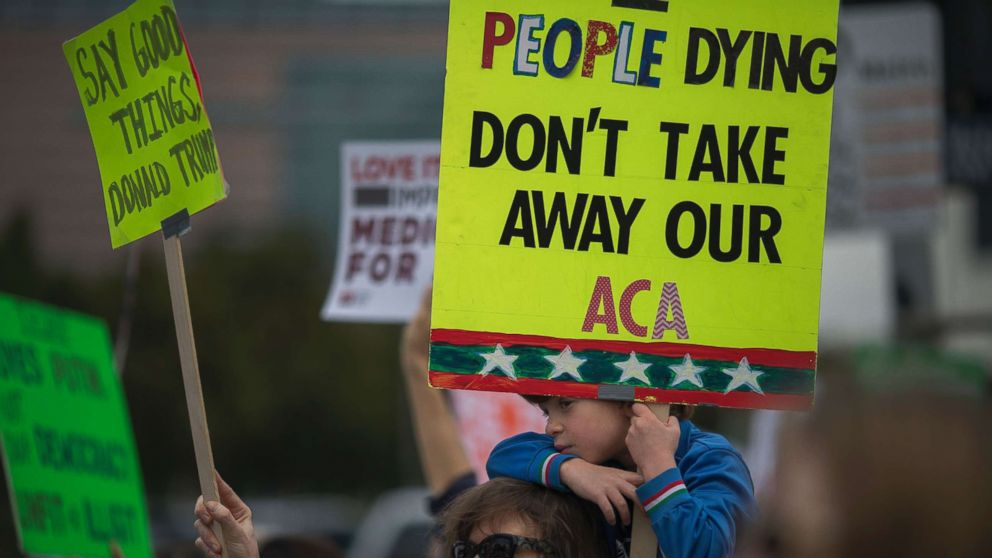 People protest Trump administration policies that threaten the Affordable Care Act, Medicare and Medicaid, near the Wilshire Federal Building, Jan. 25, 2017, in Los Angeles.