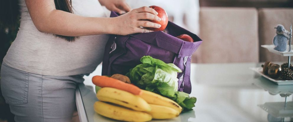 PHOTO: A pregnant woman removes fruit and vegetables from her shopping bag in an undated stock photo.