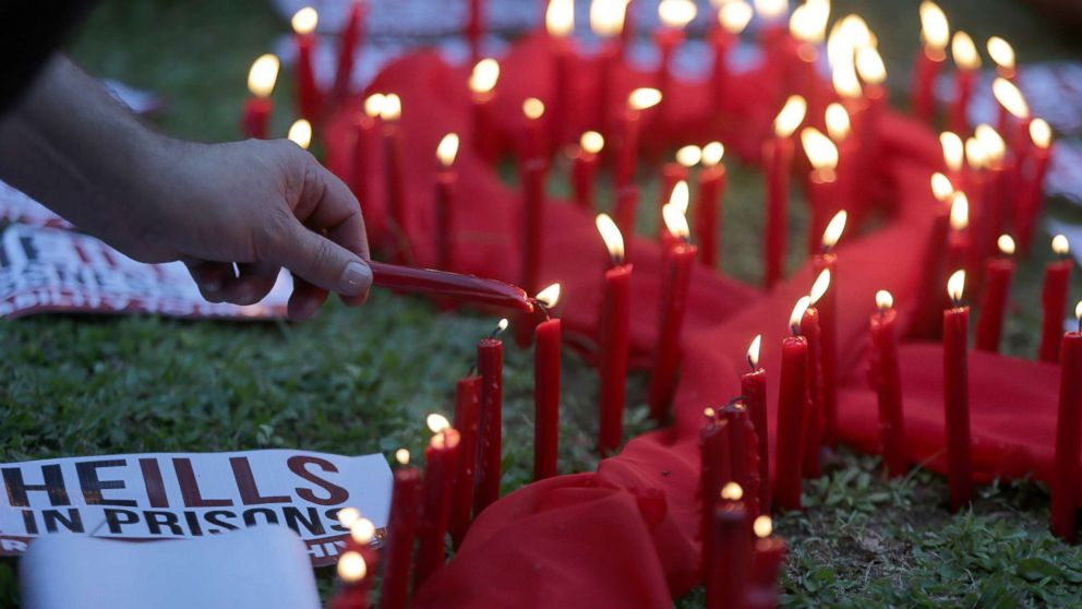 A man lights candles on a red ribbon shaped cloth in observance of the World AIDS Day in Quezon City, the Philippines, Dec. 1, 2016.