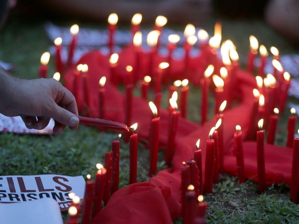 PHOTO: A man lights candles on a red ribbon shaped cloth in observance of the World AIDS Day in Quezon City, the Philippines, Dec. 1, 2016.