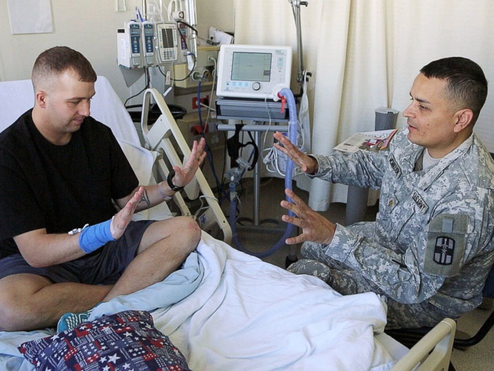 Brian McMillion talks to a recently-wounded soldier at a U.S. medical center in Germany.