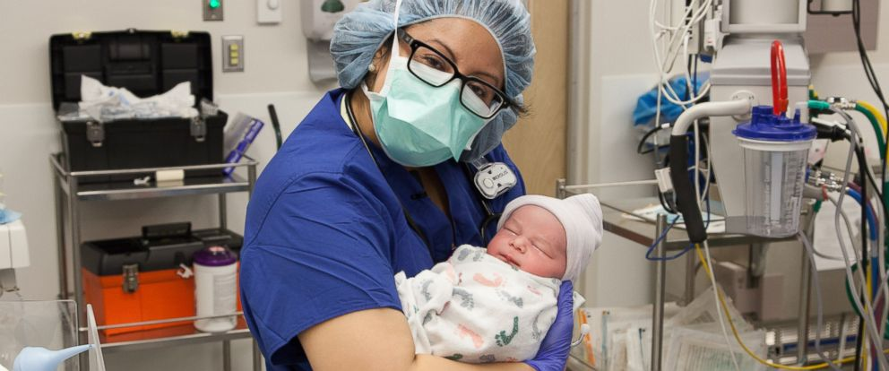 PHOTO: Naomi Cross carries baby Felix to his mom, moments after his birth.
