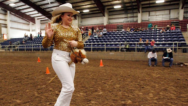 PHOTO: Jaclynn Brooks smiles and waves as she rides her stick horse.