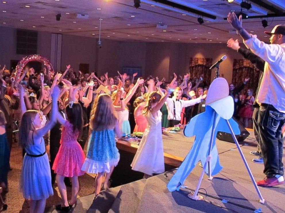 PHOTO: Promgoers put their hands in the air at a free prom just for them.